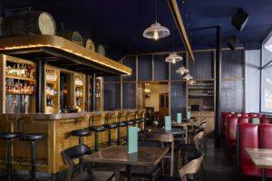 Os barris com destilados ficam suspensos acima do bar, que também serve pratos inspirados em pubs ingleses. (crédito: divulgação).