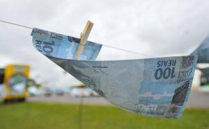 Cédula de R$ 100 pendurada em um varal.